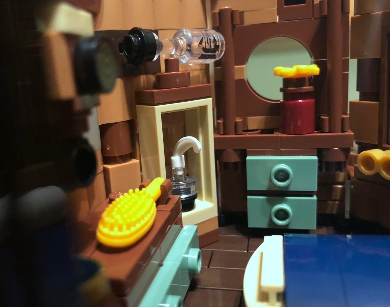 A close up photo of the Lego Tree House set, interior bedroom with bed right, dresser center back, and hairbrush seen at left. At above left, a small bottle with a ship printed on it, showing an imaginary ship in a bottle.